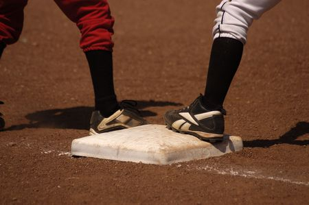baseman: Opposing players wait on first base during a youth baseball game.