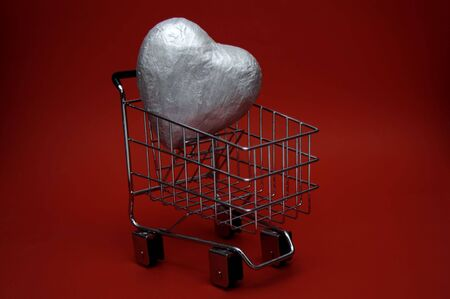 A large silver heart inside a shopping cart. Could represent a love for shopping or an attempt to buy love. Stock Photo - 704902