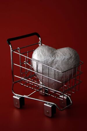 A large silver heart in a shopping cart against a deep red background. Could represent a love of shopping or trying to buy love. Stock Photo - 704908
