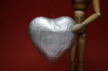 A manikin holds up a large silver heart against a deep red background. Reklamní fotografie - 704841