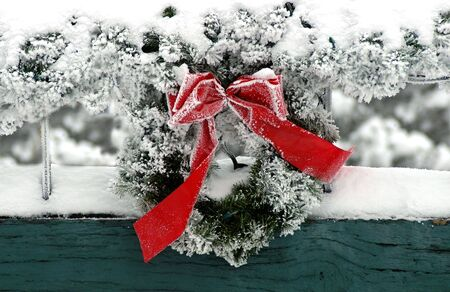 A Christmas wreath with red ribbon surrounded by winter snow. Foto de archivo