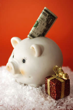 christmas savings: Money sticking out of a piggy bank with christmas gift. Could represent christmas savings.