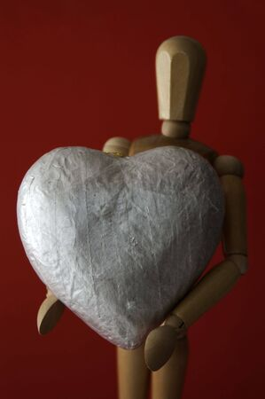A manikin holds an oversized large silver heart against a rich red background.