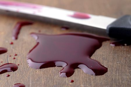 A red liquid puddle with knife. Could represent juice or blood.