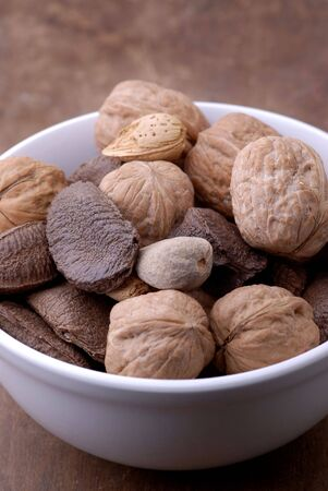A bowl of mixed nuts on an aged, old-fashioned wooden tablecutting board.