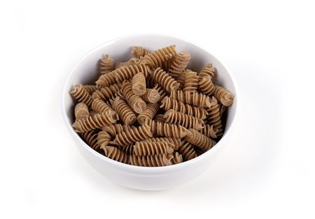 A bowl of wholewheat Rotini Pasta isolated against white.