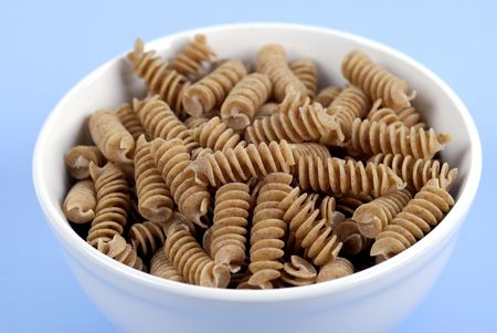 A bowl of wholewheat Rotini Pasta on a fresh, light-blue background. Imagens