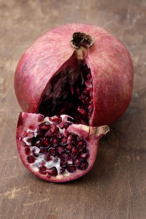 A sliced open pomegranate on an aged wooden tablecutting board.