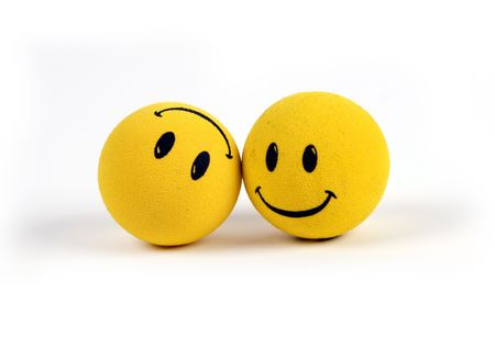 Two round smiley faces - one with a smile, one upside down with a frown. Foto de archivo