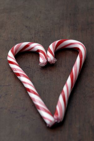 Two striped candy canes shaped into a heart on an aged wooden background. photo