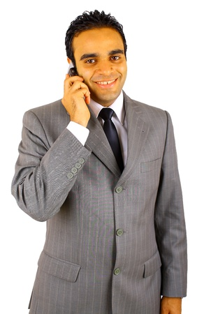 Smiling young businessman using mobile phone against white background photo