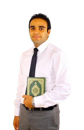 Smiling young man holding Quran isolated on white photo