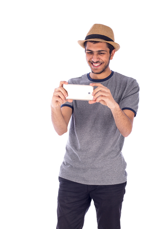 Happy friendly young man taking photo by  mobile phone, guy wearing gray t-shirt and jeans with beige hat, isolated on white background