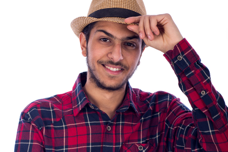 Cropped shot of a smiling young man looking confidently and holding a beige hat by his hand, guy wearing red caro shirt, isolated on white background