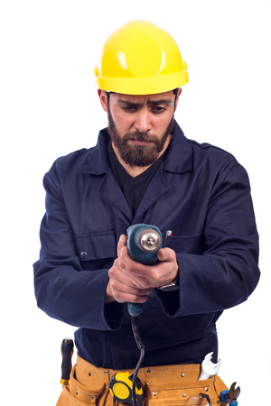 Smiling beard young worker drilling by driller tool, man wearing workswear and belt equipment, isolated on white background Imagens