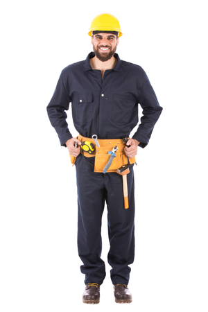 Full length shot of happy beard worker smiling and standing confidently, guy  wearing dark blue workwear and belt equipment with yellow helmet, isolated on white background