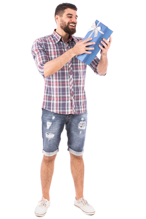 Handsome happy young man smiling and opening a blue gift box, guy wearing caro shirt and short jeans with white shoes, isolated on white background