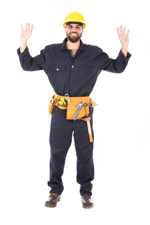 Full length shot of happy beard worker smiling and rising his hands,  guy wearing dark blue workwear and belt equipment with yellow helmet, isolated on white background Banco de Imagens