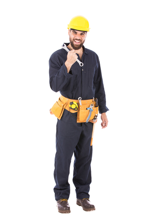 Full length shot of happy beard worker smiling and holding an english key, guy  wearing dark blue workwear and belt equipment with yellow helmet, isolated on white background