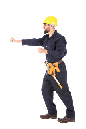 Full length shot of happy beard worker looking side and hitting something, guy wearing dark blue workwear and belt equipment with yellow helmet, isolated on white background