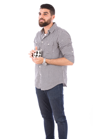 Handsome happy beard man smiling and holding a mug, guy wearing gray shirt and jeans, isolated on white background