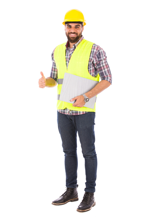 Happy beard engineer holding a clipboard and thumbs up, guy wearing caro shirt and jeans with yellow vest and helmet, isolated on white background Banco de Imagens