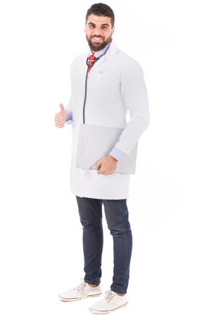 Full length shot of a happy beard doctor in white lab coat with stethoscope holding a clipboard and thumbs up, isolated on white background Banco de Imagens