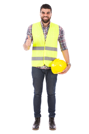 Happy beard engineer holding a yellow helmet and thumbs up, guy wearing caro shirt and jeans with yellow vest, isolated on white background
