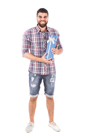 Handsome happy young man smiling and holding a blue gift box, guy wearing caro shirt and short jeans with white shoes, isolated on white background Banco de Imagens
