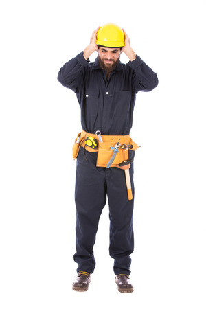 Full length shot of happy beard worker smiling and holding his head,  guy wearing dark blue workwear and belt equipment with yellow helmet, isolated on white background Banco de Imagens