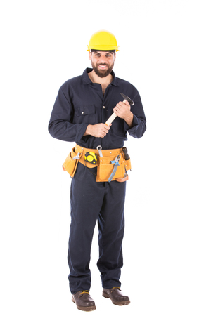 Full length shot of happy beard worker smiling and holding a hammer, guy  wearing dark blue workwear and belt equipment with yellow helmet, isolated on white background