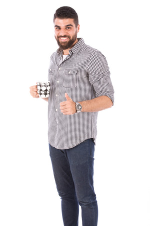 Handsome happy beard man holding a mug and thumbs up, guy wearing gray shirt and jeans, isolated on white background