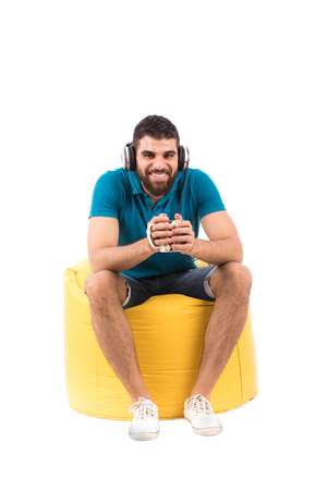 Handsome happy young man with headphones sitting on a yellow chair and listening to music, guy holding amug and wearing clay shirt and short jeans with white shoes, isolated on white background