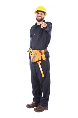 Full length shot of happy beard worker smiling and pointing to you, guy  wearing dark blue workwear and belt equipment with yellow helmet, isolated on white background