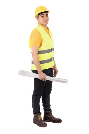 Full length shot of a happy young engineer smiling and holding and holding a rolled paper, guy wearing yellow t-shirt and jeans with yellow vest and helmet, isolated on white background