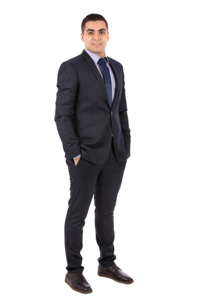 Full length shot of a happy handsome young businessman with hand in pocket smiling and standing confidently, guy wearing dark blue  suit and blue tie, isolated on white background Banco de Imagens
