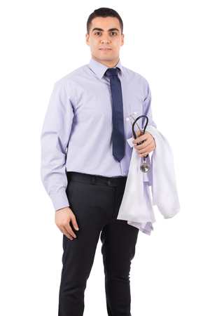 Happy young doctor smiling and holding a white coat and stethoscope, guy wearing a classic shirt and trousers with a blue tie, isolated on white background