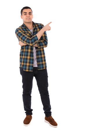 Full length shot of a happy handsome young man smiling and pointing to something, guy wearing caro shirt and jeans with brown shoes, isolated on white background