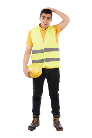 Full length shot of a happy young engineer putting his hand on his head and holding yellow helmet, guy wearing yellow t-shirt and jeans with yellow vest, isolated on white background