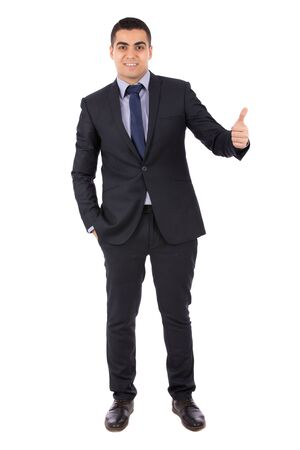 Full length shot of a happy handsome young businessman with hand in pocket smiling and thumbs up, guy wearing dark blue  suit and blue tie, isolated on white background