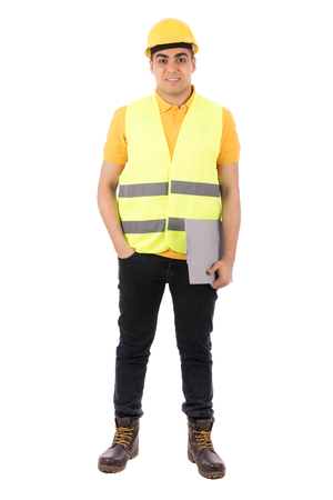 Full length shot of a happy young engineer smiling and holding and holding a clipboard, guy wearing yellow t-shirt and jeans with yellow vest and helmet, isolated on white background