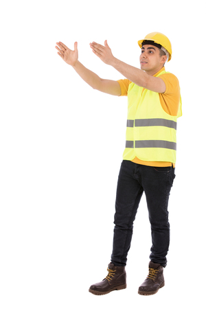 Full length shot of a happy young engineer smiling and holding and rising his hands, guy wearing yellow t-shirt and jeans with yellow vest and helmet, isolated on white background Banco de Imagens
