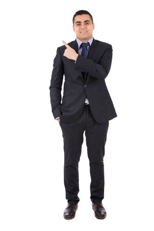 Full length shot of a happy handsome young businessman with hand in pocket smiling and pointing to something, guy wearing dark blue  suit and blue tie, isolated on white background