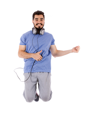 Handsome happy excited beard young man jumping and acting play guitar, guy wearing blue t-shirt, isolated on white background