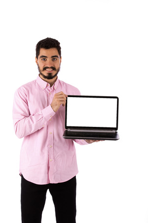 Handsome happy beard young man smiling and holding a laptop, guy wearing pink shirt, isolated on white background Banco de Imagens