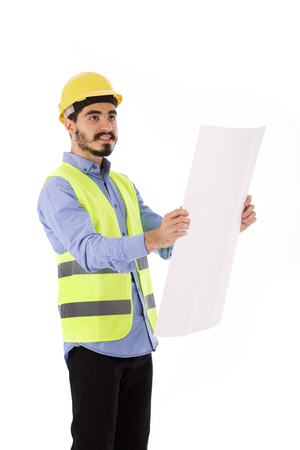 Happy beard engineer smiling and holding a paper, guy wearing blue shirt and yellow vest with a helmet, isolated on white background