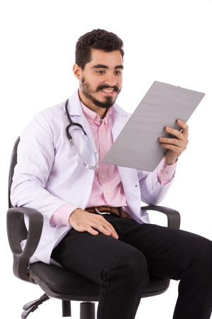 Happy beard young doctor in white lab coat with stethoscope sitting on a chair and reading some notes, isolated on white background