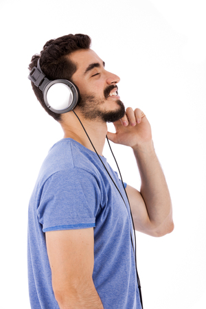 Side shot of handsome happy beard young man smiling and listening to music, guy wearing blue t-shirt, isolated on white background Banco de Imagens