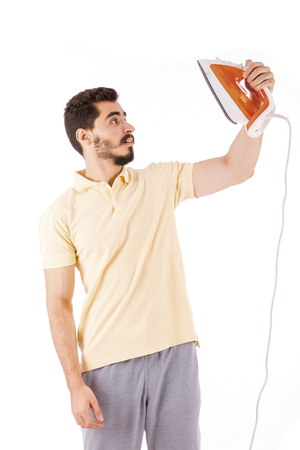 Handsome happy beard young man looking side and holding an iron, guy wearing beige t-shirt, isolated on white background Banco de Imagens