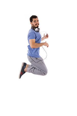 Side shot of handsome happy excited beard young man jumping and acting play guitar, guy wearing blue t-shirt, isolated on white background